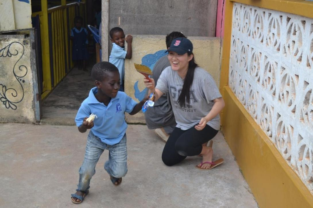 A teenager under the age of 18 spends time with children in Ghana during her first volunteer trip.